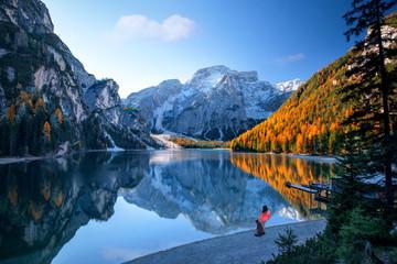 Touristin mit Hund bestaunen wunderschönen Ausblick auf einen Bergsee umgeben von Felsen