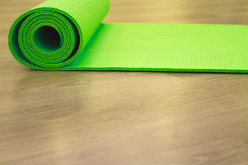 Yoga mat on wooden floor
