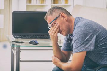 Tired freelancer man rubbing his eyes