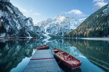 Klarer Gebirgssee mit Booten und Steg  vor felsiger Gebirgslandschaft