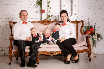 Big happy family: mother, father, triplets sons