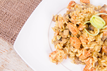 Risotto with mushrooms and chicken decorated with leek on a wooden background