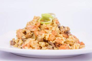Risotto with mushrooms and chicken decorated with leek on a white background