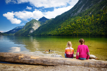 Fototapete - Two cute sisters enjoying the view of deep green waters of Konigssee, known as Germany's deepest and cleanest lake, located in the extreme southeast Berchtesgadener Land, Bavaria