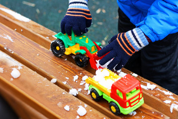 Child plays with toy cars in the first snow.