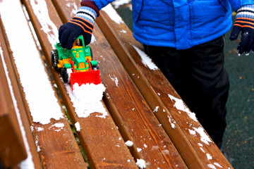The child plays with the snow on the bench.
