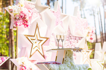 Two glasses of champagne with wedding ceremony stage decoration in the background