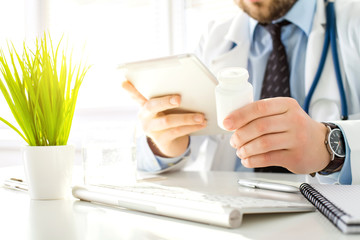 Doctor uses the tablet while sitting in his office