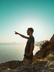 Young Man Standing on top of a Cliff, pointing into the distance