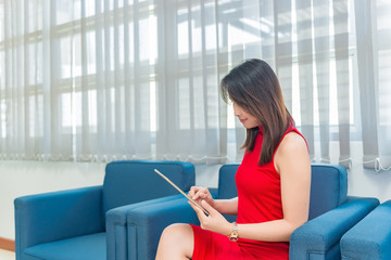 Business girl in red dress sit on sofa for work on laptop,business woman work in office concept