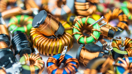 Colorful coils with magnetic core and copper winding. Beautiful background from inductors with small depth of sharpness. Concept for research, development, science and technology.