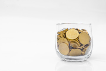 Many  gold coins in glass on white background