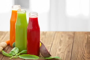 Bottles with various fresh vegetable juices and ingredients on table
