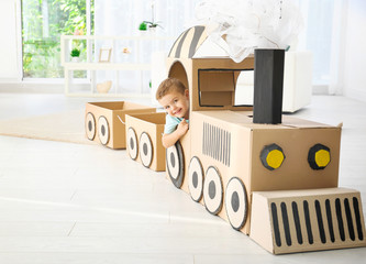 Little boy playing with cardboard train in light room