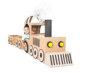 Little boy playing with cardboard train on white background