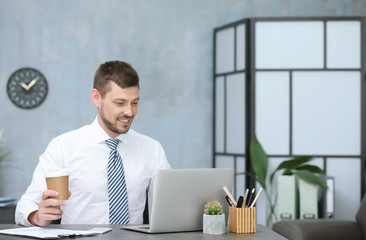 Handsome businessman drinking coffee while working in office