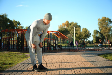 Sporty young man resting after jumping rope in park