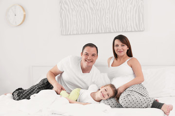Happy young family on bed at home
