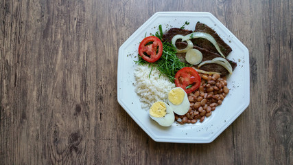 Brazilian typical food dish with beans, rice, sun meat, egg, lettuce, tomato and onion.