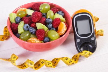Fruit salad, glucometer for measuring sugar level and centimeter, diabetes and healthy nutrition concept