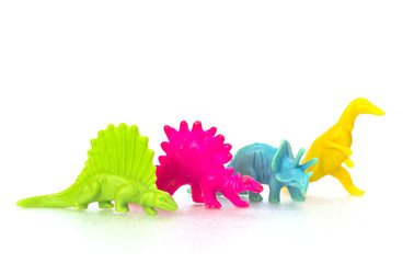 Small colorful dinosaur toy on white background in a row