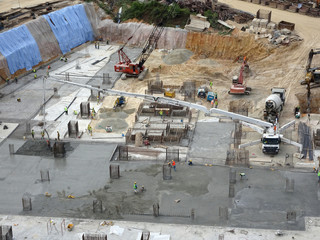 Construction workers pouring wet concrete using concrete hose from concrete pumping machine into floor slab form work at the construction site.