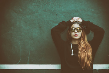 Asian hipsters girl posing for take a photo,lifestyle of modern woman,Thai people in hippie style,Golden hairs,young lovely gold woman on green wall,dark tone