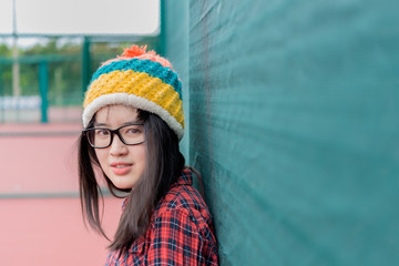 Close up hipster pose for take a photo on wall,lifestyle of teenage,thailand people,young woman posing on fence