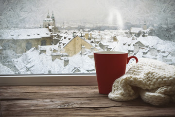 Frozen window and a red cup with a scarf on the windowsill with a beautiful view of winter Prague