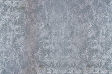 A beautiful pattern of frost on window glass in winter, shooting macro, abstract background