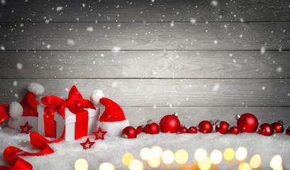 Weihnachten Hintergrund mit Holz, Geschenk, Weihnachtsmützen, Kugeln, Lichterkette und Schnee