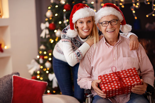 daughter and elderly father in wheelchair celebrating Christmas together.