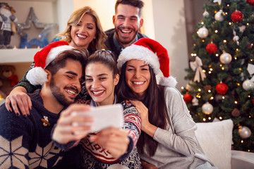 .smiling friends taking photo with mobile phone for Christmas.
