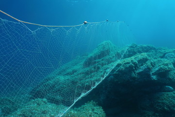 Underwater rocky seabed with a fishing net (gillnet) in the Mediterranean sea, Cap de Creus, Cadaques, Catalonia, Costa Brava, Spain
