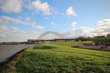 Bridge over river the Noord in the Netherlands with blue sky and big white clouds