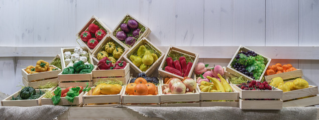 Decorative vegetables, fruits and berries lie in square boxes on the counter.