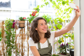Young woman taking selfie on her city garden balcony - Technology and nature theme