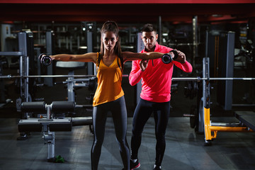 Beautiful shape young girl in sportswear doing shoulders exercise with dumbbells while personal trainer standing next to her and looking at the camera in the gym.