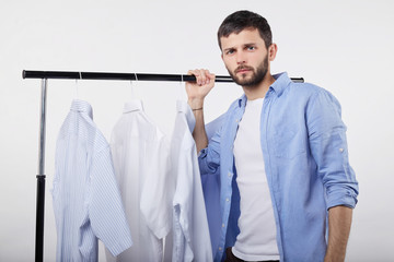 Nothing to wear concept. Handsome young bearded man dressed casually feeling frustrated standing among same colored clothes in his wardrobe, trying to choose what to wear on a date with his girlfriend