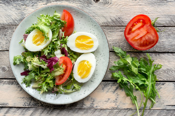 Vegetable salad with sliced boiled eggs, tomato and fresh lettuce and arugula served on wooden table. Top view.