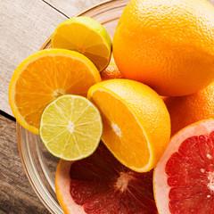 Citrus fruits - oranges, limes, grapefruits. On wooden background. square
