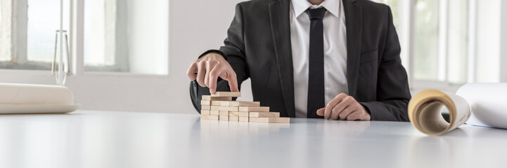 Businessman in black suit building steps of wooden blocks
