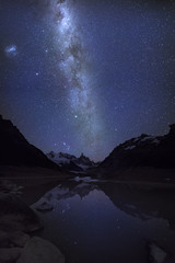 Fantastic quiet starry night on the glacial lake near Mountain peak Cerro and Lagoon Torre. Milky Way and the Magellanic Cloud. Patagonia, Argentina, Andes.