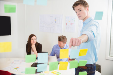 Businessman Explaining Notes To Colleagues In Office