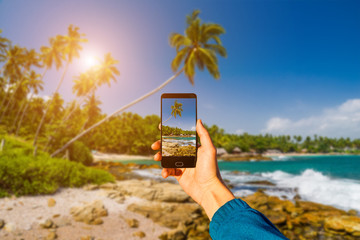 Photographing with smartphone in hand. Travel concept. Sunset on a tropical beach