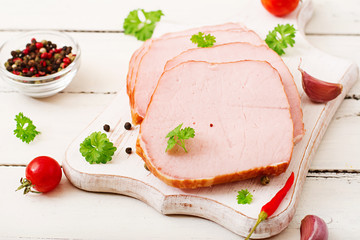 Slices of ham on white wooden background. Flat lay. Top view