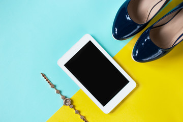 Tablet, fashion concept, on a blue and yellow background. Copy space. Top view.