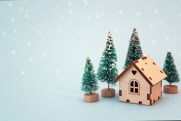 Christmas and New Year miniature  house with fir trees on blue background. Copy space for text. Winter card.
