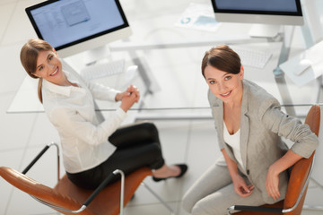 view from the top. two women colleagues sitting near the desktop