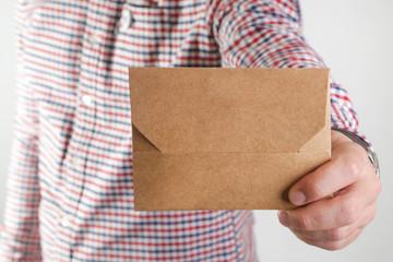 Man holding blank brown paper envelope